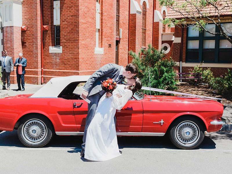 Ein Ehepaar nach der Hochzeits vor der Kirche. Hochzeitsauto mieten: das perfekte Auto für Ihre Hochzeit.