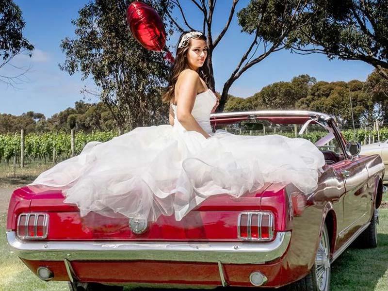 Eine Braut die in einem Hochzeits-Auto sitzt. Von der Oldtimervermietung.